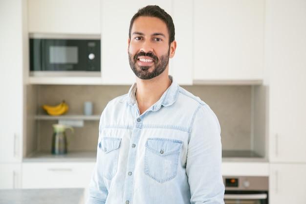 Het vrolijke aantrekkelijke donkerharige latijnse mens stellen in keuken Gratis Foto