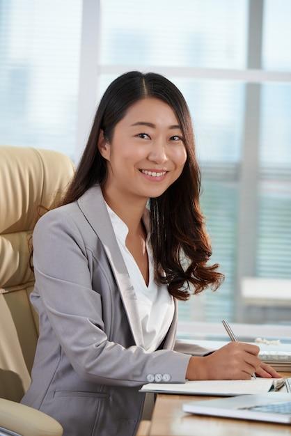 Het vrolijke aziatische bedrijfsvrouw stellen bij bureau in bureau Gratis Foto