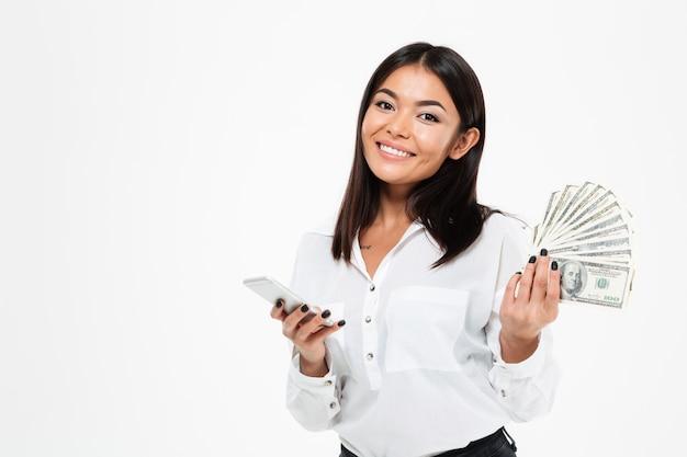 Het vrolijke jonge aziatische geld van de vrouwenholding die mobiele telefoon met behulp van. Gratis Foto