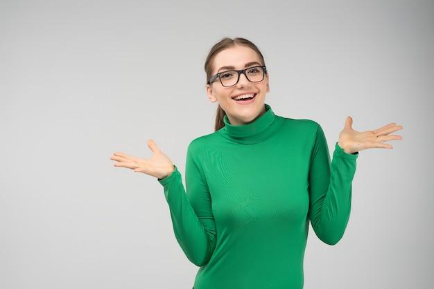 Het vrolijke jonge meisje stellen in studio haalt in verrassing op Premium Foto