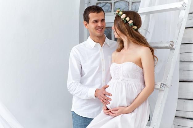 Het vrolijke jonge paar kleedde zich in wit thuis status Gratis Foto