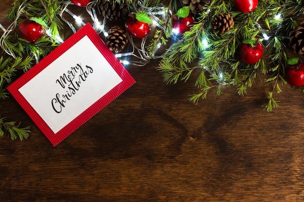 Het vrolijke model van de kerstkaart op houten achtergrond Gratis Foto