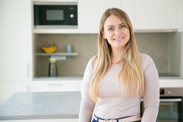 Het vrolijke mooie eerlijke haired jonge vrouw stellen in keuken Gratis Foto