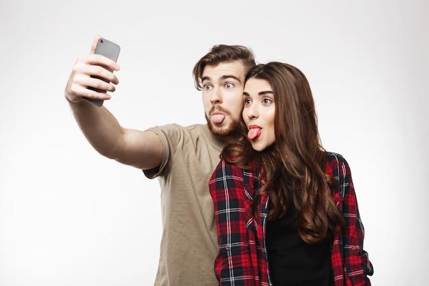Het vrolijke paar neemt selfies op telefoon die gezichten maken, hebbend pret Gratis Foto