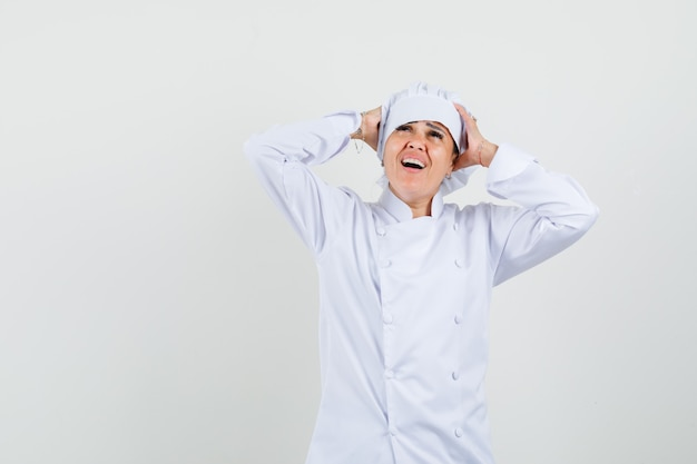 Het vrouwelijke chef-kok die hoofd binnen dient in wit uniform en gelukkig kijkt Gratis Foto