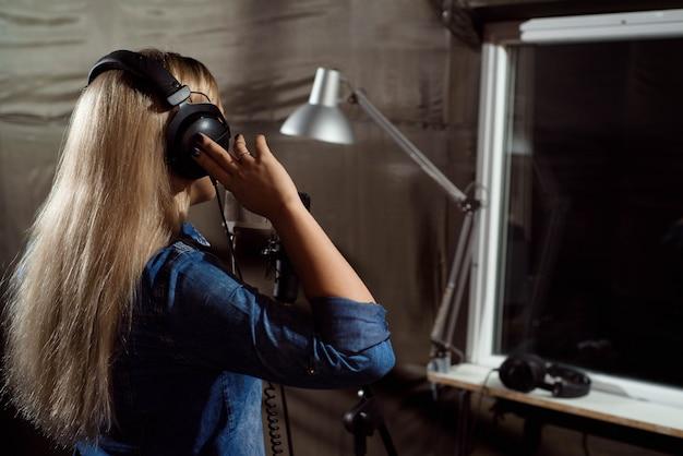 Het vrouwtje zingt met mobiele telefoon bij opnamestudio. u Premium Foto