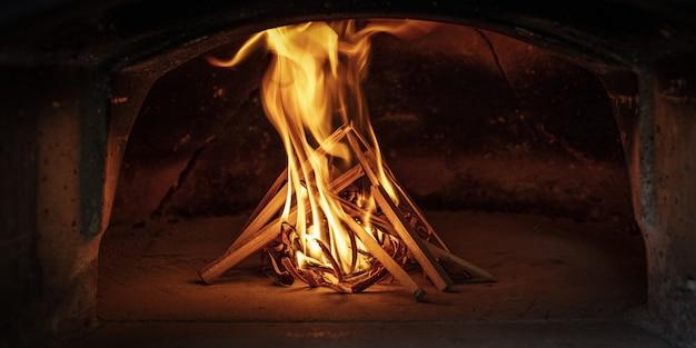 Het vuur aansteken in een traditionele houtoven Premium Foto