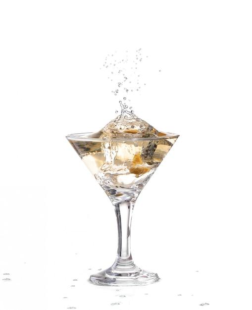 Het water kabbelt en spatte als een groene spaanse olijf met peper in het glas valt Premium Foto