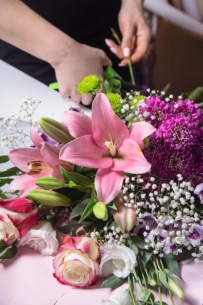 Het werk van de bloemist in het proces van het creëren van een boeket met lelies op de werkplek Premium Foto