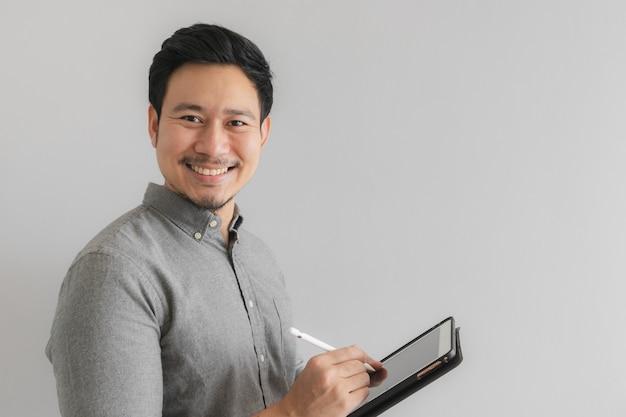 Het werk van de gelukkige en glimlachondernemerszakenman op zijn tablet met grijze achtergrond. Premium Foto