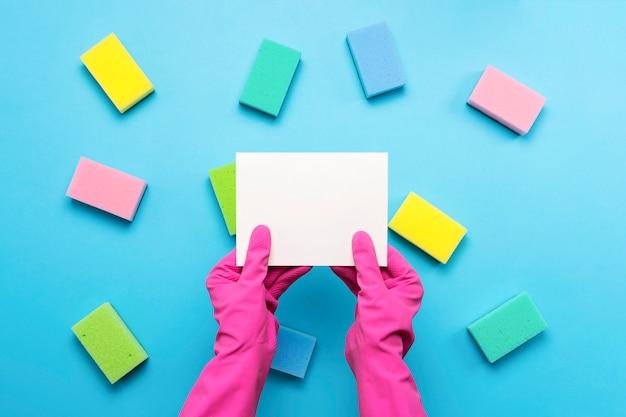 Het wijfje dient roze rubberhandschoenen in houdt een lege kaart op een blauwe achtergrond met sponsen. schoonmaak service concept. kopieer ruimte. plat lag, bovenaanzicht Premium Foto
