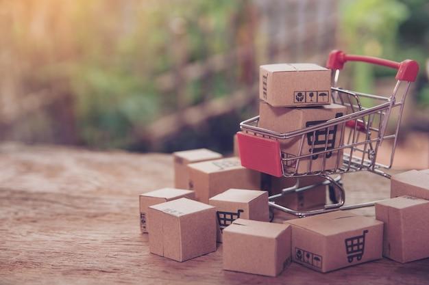Het winkelen concept - kartons of document vakjes in boodschappenwagentje op bruine houten lijst. online winkelen consumenten kunnen thuis winkelen en bezorgservice. met kopie ruimte Premium Foto