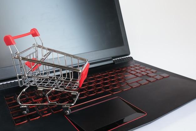 Het winkelen online concept - boodschappenwagentje op het zwarte toetsenbord. rode metalen trolley op een laptop toetsenbord Premium Foto