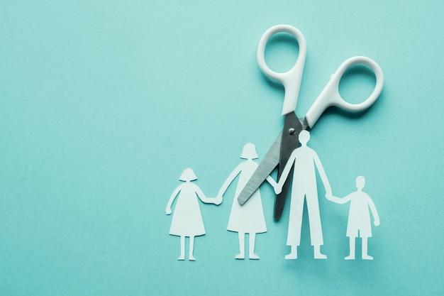 Het witte document van de schaar scherpe familie dat op blauwe achtergrond wordt verwijderd Premium Foto