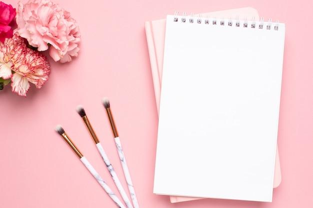 Het witte en roze notitieboekje met anjerbloem en maakt omhoog borstels op een roze achtergrond Premium Foto