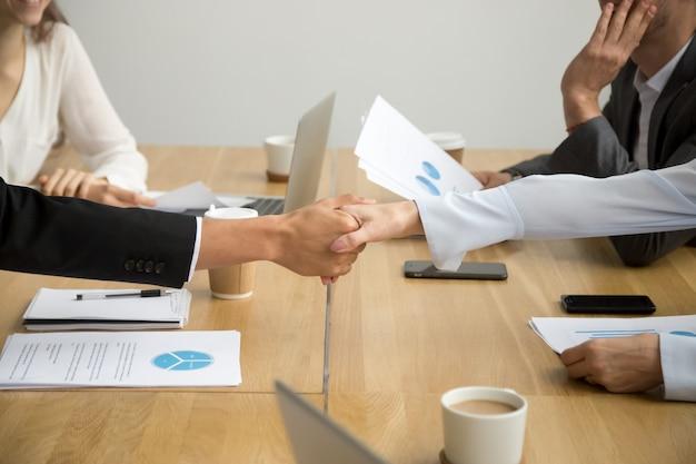 Het witte vrouwelijke en zwarte mannelijke handen schudden, sluit omhoog mening Gratis Foto