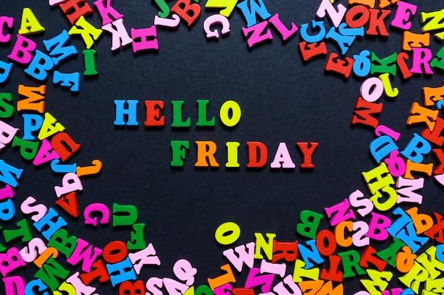 Het woord hello friday uit veelkleurige houten letters op een zwarte achtergrond Premium Foto