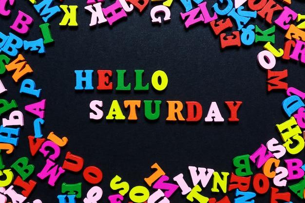 Het woord hello saturday van veelkleurige houten letters op een zwarte achtergrond Premium Foto