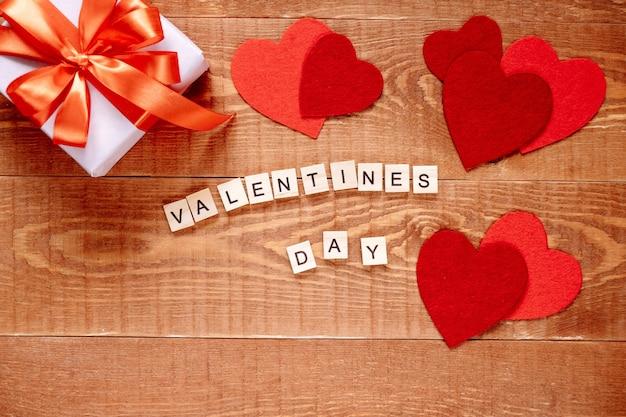 Het woord valentijnsdag. liefde op houten blokken op natuurlijke achtergrond. thema van liefde, hart en cadeau. Premium Foto