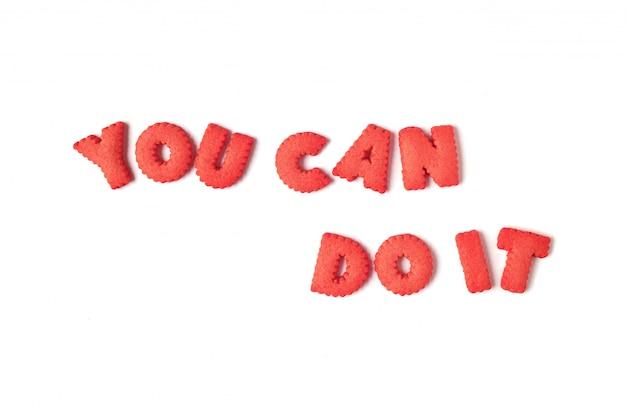 Het woord you can do it gespeld met roodgekleurde alfabetvormige koekjes Premium Foto