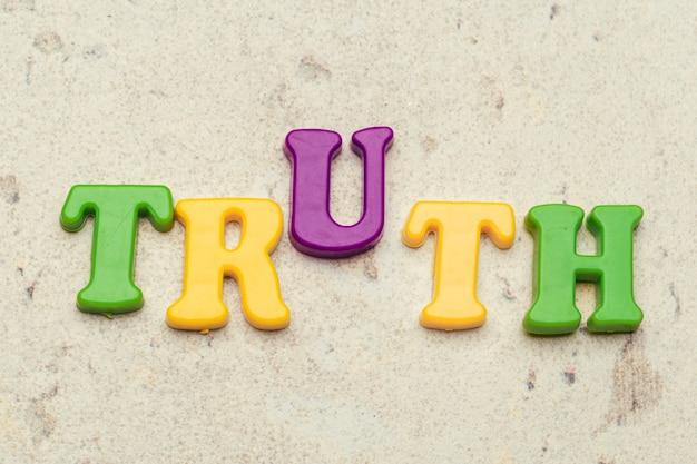 Het woordconcept van de waarheid in plastic kleurrijke brieven Premium Foto