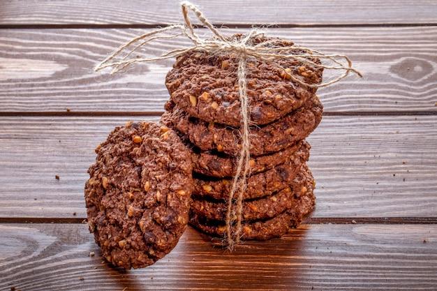 Het zijaanzicht van chocoladeschilferkoekjes met graangewassennoten en cacao bond met een kabel op houten achtergrond Gratis Foto
