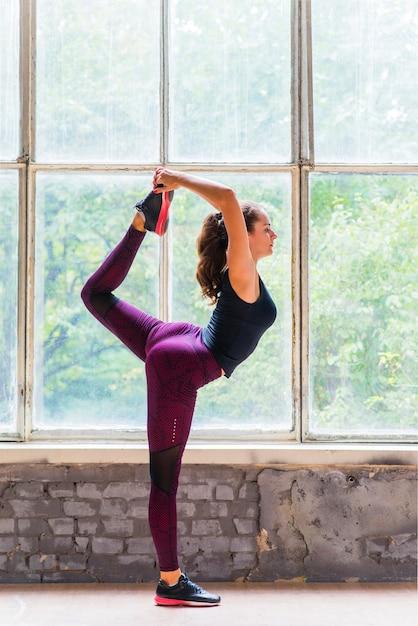 Het zijaanzicht van jonge vrouw die yoga doen stelt dichtbij het glasvenster Gratis Foto