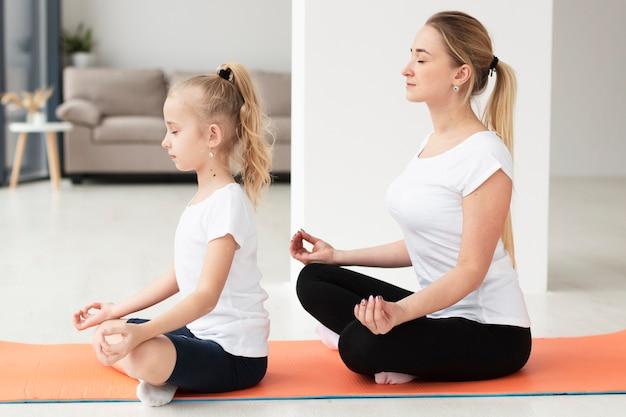 Het zijaanzicht van moeder en dochter die een yoga doen stelt thuis Gratis Foto