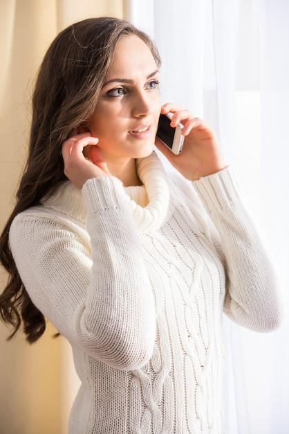 Het zijaanzicht van mooie vrouw spreekt op telefoon. Premium Foto