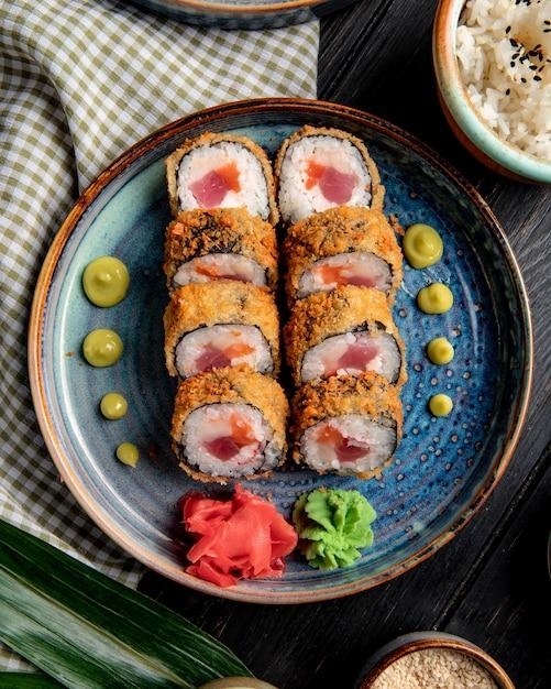 Het zijaanzicht van sushi rolt met krab en tonijn op een plaat met gember en wasabi op hout Gratis Foto