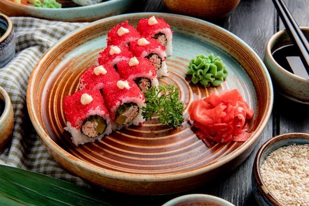 Het zijaanzicht van sushi rolt met krabavocado bedekt met rode kaviaar met gember en wasabi op een plaat op hout Gratis Foto