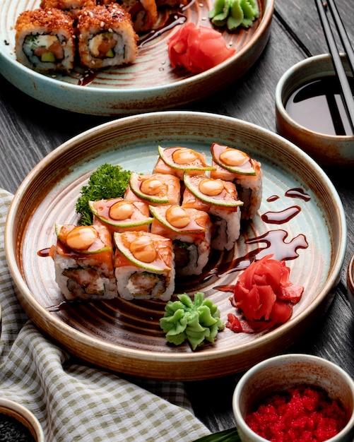 Het zijaanzicht van sushibroodjes met garnalenavocado en roomkaas diende met gember en wasabi op een plaat op hout Gratis Foto