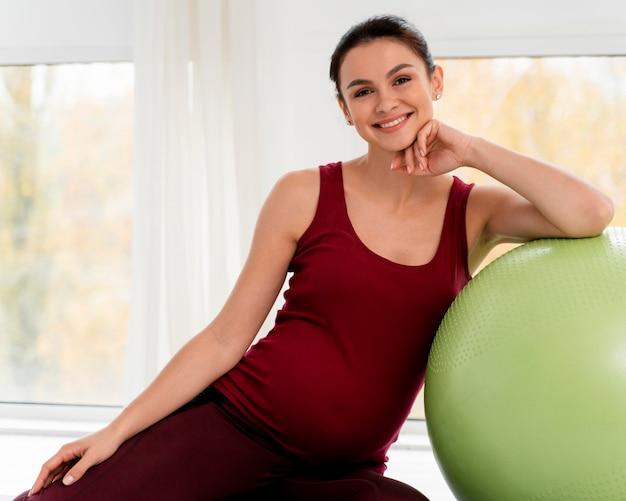 Het zwangere vrouw stellen naast geschiktheidsbal Gratis Foto