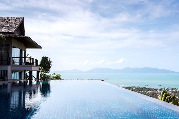 Het zwembadmening van de oneindigheid over berg met wolken en blauwe hemel Premium Foto