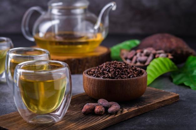 Hete cacao thee. verse kruidenthee van warme chocolademelk gemaakt van cacaoboonvlokken, rijk aan flavonoïden en antioxidanten, geserveerd in glazen, selectieve aandacht Premium Foto