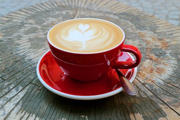 Hete cappuccinokoffie in rode die kop op de lijst van de boomstomp wordt gediend Premium Foto