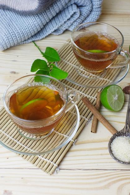 Hete citroentheeglazen met pijpje kaneel op bamboemat en ambacht. Premium Foto