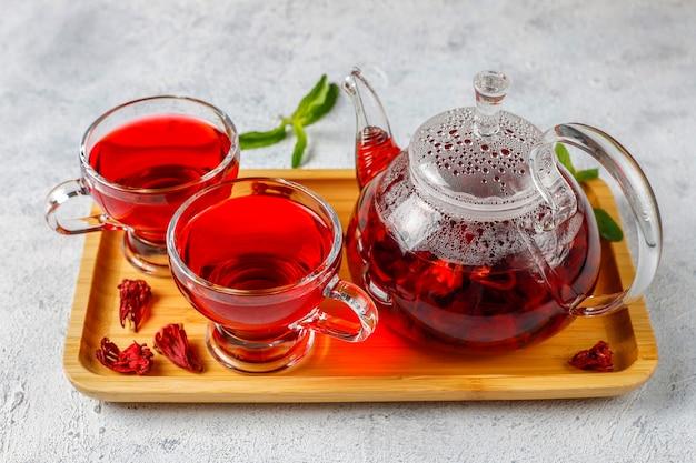 Hete hibiscus thee in een glazen mok en glazen theepot. Gratis Foto