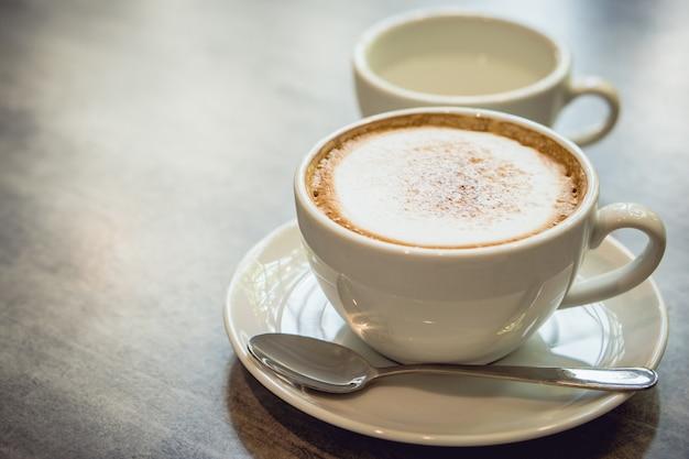 Hete koffie en hete theeplaats op de marmeren lijst in vroege ochtend met copyspace Premium Foto