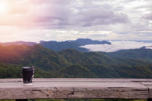 Hete koffie op houten tafel met nevelig bos in ochtendhemel. Premium Foto
