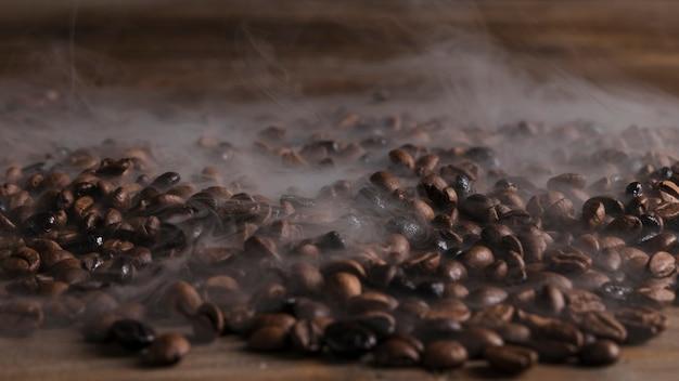 Hete koffiebonen op houten lijst Premium Foto