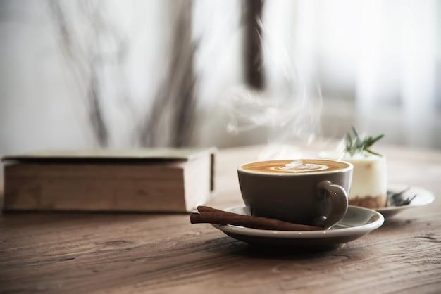 Hete koffiekop die op houten lijst wordt geplaatst Gratis Foto