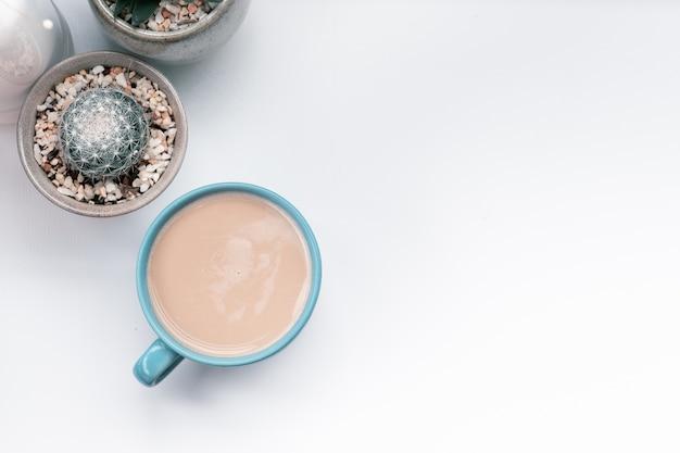 Hete koffiekop met cactus op de voorwerpen van de aardewerkdecoratie. mobiele koffiemok op witte lijst Premium Foto