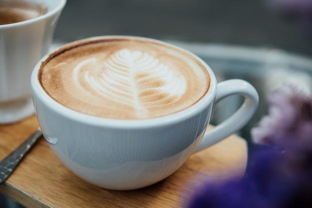 Hete latte kunst in koffiekop op houten lijst in koffiewinkel Gratis Foto