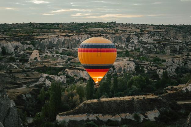 Hete luchtballon die over cappadocia bij dageraad vliegt Premium Foto