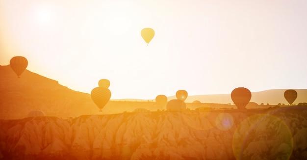 Hete luchtballon die over rotslandschap in cappadocia turkije vliegt Premium Foto