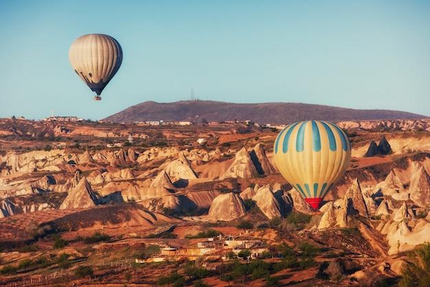 Hete luchtballon die over rotslandschap in cappadocia turkije vliegt. Premium Foto