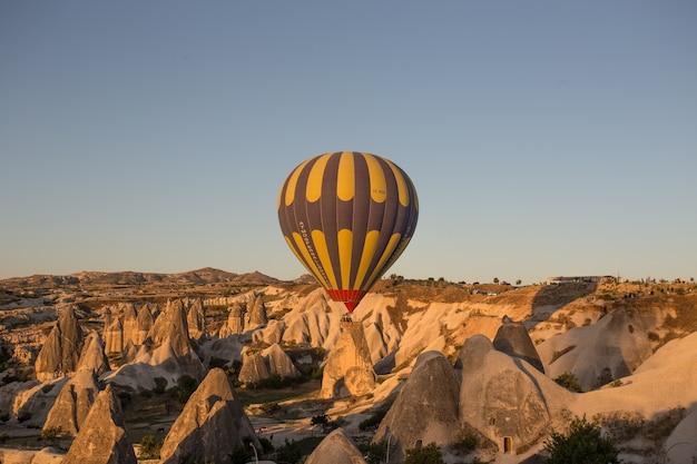 Hete luchtballons over de heuvels en de velden tijdens zonsondergang in cappadocië, turkije Gratis Foto