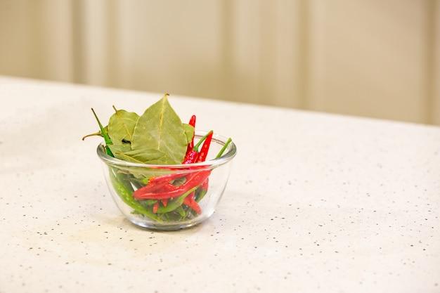 Hete rode en groene paprika's met kruiden in een kom voor smakelijke chilisaus in kom Premium Foto