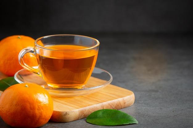 Hete sinaasappelthee en verse sinaasappel op tafel Gratis Foto